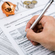 Stock Photo: Man hand filling PIT-11 income tax forms with piggybank and coin