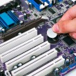 图库照片: Hand install battery to PC motherboard