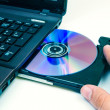Man insert compact disc from laptop — Stock Photo