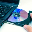 Man insert compact disc from laptop — Stock Photo #32751013