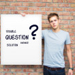 Young man holding whiteboard with question and solution words — Stock Photo