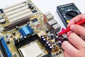 Motherboard measure. Man repairing computer hardware — Stock Photo