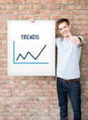 Young man holding whiteboard with trends chart — Stock Photo