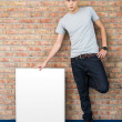 Young man holding blank whiteboard — Stock Photo