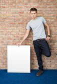 Young man holding blank whiteboard — Стоковое фото