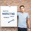 Young man holding whiteboard with marketing content. Business pr — Stock Photo