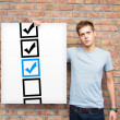 Young man holding whiteboard with check boxes — Stock Photo