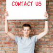 Young man holding whiteboard with contact us words — Stockfoto