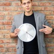 Young businessman holding a clock on brick wall background.  — Stock Photo