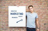 Young man holding whiteboard with marketing content. Business pr — Foto Stock