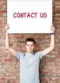 Young man holding whiteboard with contact us words — Stock Photo