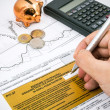 Stock Photo: Mhand filling PIT-37 income tax forms with calculator and coi