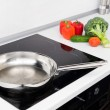 Frying pan and vegetables in modern with induction stove — Stock Photo