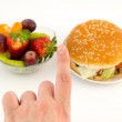 Finger choosing between hamburger and fruits. Food on white back — Stock Photo