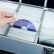 Hand pulls disc from aluminum carrying CD-DVD case — Stock Photo #51350469