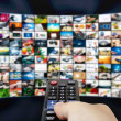 Big LCD panel with television stream images and remonte control — Stock Photo #51350523