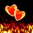 Two loving hearts, burning in the flames of love - Stock Photo