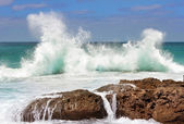 Sea wave crashing on rocks — Stock Photo