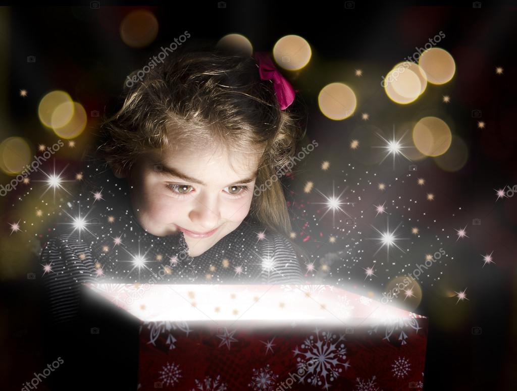 Child opening a magic gift box with lights and shining around  Stock Photo #16944647
