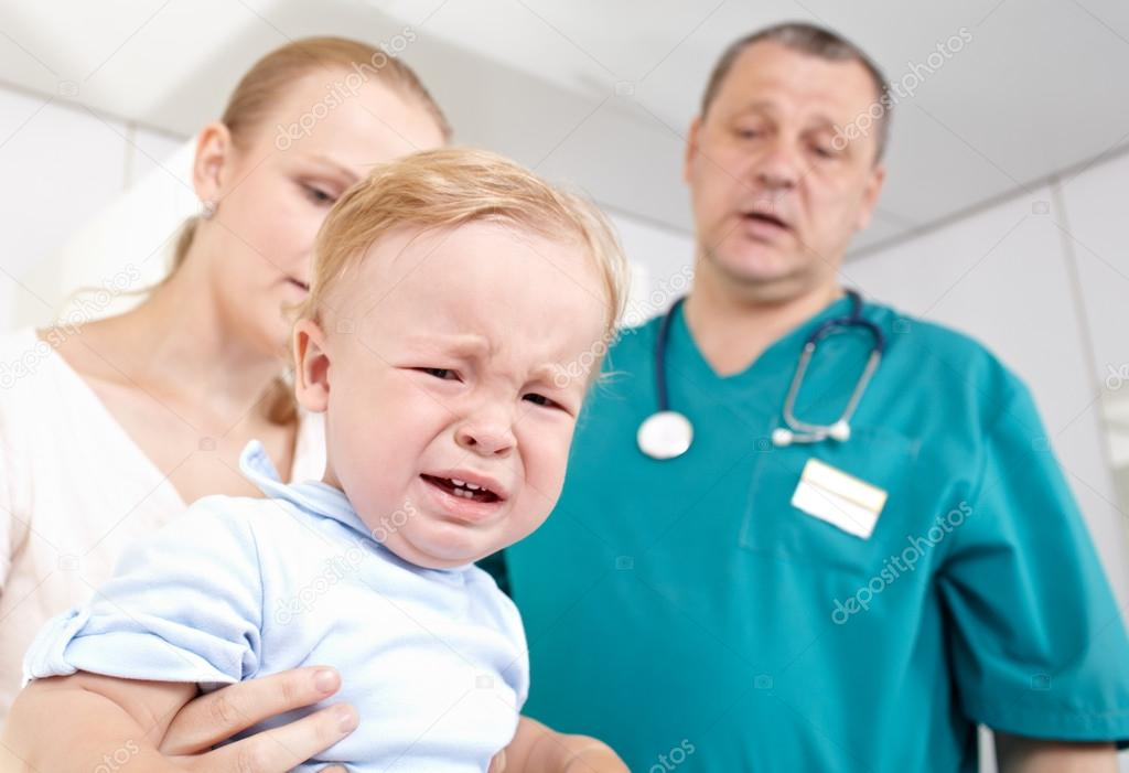 A 1,5 year-old boy is frightened and crying in a medical study.   Stock Photo #12647414