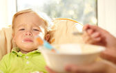 Kid is very disappointmented about porridge. — Stock Photo