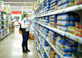 Woman in the supermarket. Kid's food. — Stock Photo