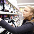 Young woman is choosing wine in the supermarket. - Stock Photo