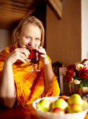 Young woman is drinking tea and smiling. — Stock Photo