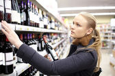 Young woman is choosing wine in the supermarket. — Stock Photo