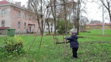 The little boy is swinging an old swing. Johvi, Estonia. — Stock Video