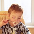 Two year old boy eats porridge in the morning. — Stock Photo