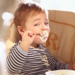 Two year old boy eats porridge in the morning. — Stock Photo #21106629