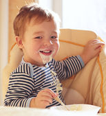 Two year old boy smiles and eating porridge. — Stock Photo