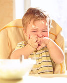 Little boy doesn't want to eat porridge. — Stock Photo
