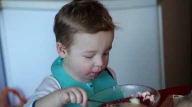 Two year old boy is eating fish soup from the plate — Stock Video