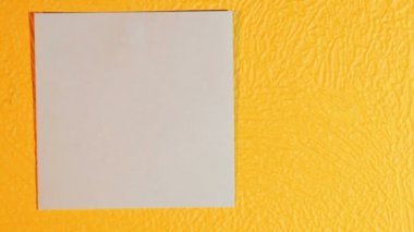 Hand sticks blank pink stick note on the yellow wall — Vídeo de stock