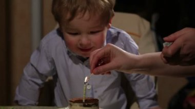 Kid's birthday. Boy blows out the candle in the tiramisu cake — Vidéo