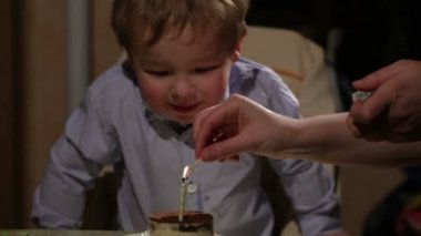 Kid's birthday. Boy blows out the candle in the tiramisu cake — Vídeo de stock