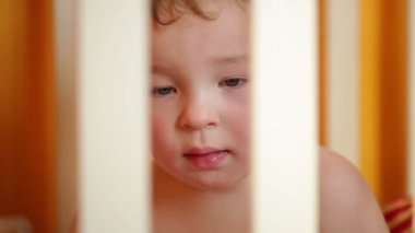 Little boy watching a film sitting in the playpen. Closeup — Stock Video