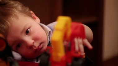 Two year old boy plays with toy trucks. Close up shot — Stock Video