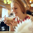 Girl is drinking latte in cafe. — Stock Photo