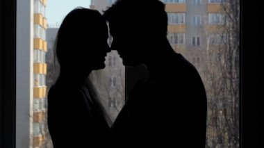 Two lovers embracing and kissing. Silhouette at the window. — Stock Video