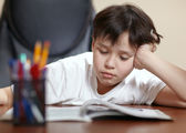 School boy studies hard over his book at home. — Stock Photo