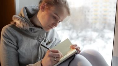 Young girl writing in her journal while sitting at a large window — Stock Video