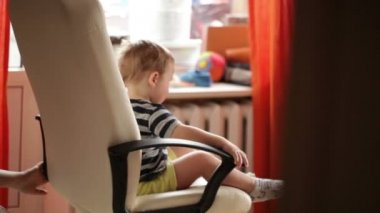 Two year old boy is spinning on chair. — Stock Video