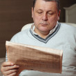 Portrait of senior man reading newspaper at home. — Stock Photo