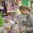 Stock Video: Young womis choosing toys for her kid.