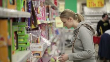 Young woman is choosing toys for her kid. — Stock Video
