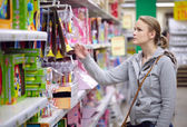 Young woman is choosing toys for her kid. — Stock Photo