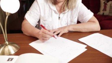 Engelska lärare skriver något sitter vid bordet. — Stockvideo